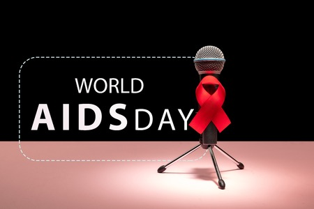 Aids Awareness Sign Red Ribbon with microphone on pink background . World Aids Day concept. The health, help, care, support, hope, illness, healthcare concept