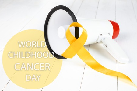 Yellow ribbon symbolic color for Sarcoma Bone cancer awareness and suicide prevention on aged wood with megaphone. The cancer, health, help, care, support, hope, illness, healthcare concept