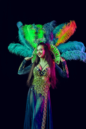 Beautiful young woman in carnival peacock costume. Beauty model woman at party over holiday background with magic glow. Christmas and New Year celebration. Glamour lady with perfect make up and hairstyle Stock Photo - 116259273