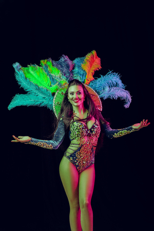 Beautiful young woman in carnival peacock costume. Beauty model woman at party over holiday background with magic glow. Christmas and New Year celebration. Glamour lady with perfect make up and hairstyle Stock Photo - 116259282