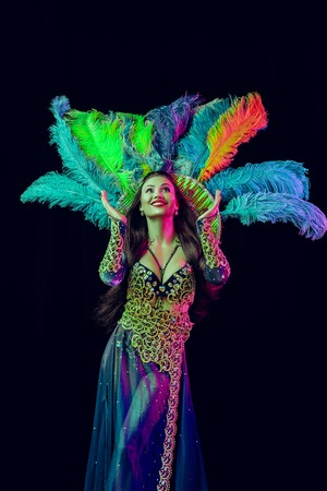 Beautiful young woman in carnival peacock costume. Beauty model woman at party over holiday background with magic glow. Christmas and New Year celebration. Glamour lady with perfect make up and hairstyle