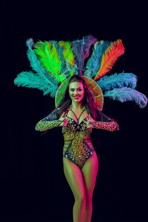 Beautiful young woman in carnival peacock costume. Beauty model woman at party over holiday background with magic glow. Christmas and New Year celebration. Glamour lady with perfect make up and hairstyle Stock Photo - 116259288
