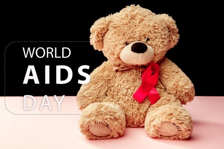 Aids Awareness Sign Red Ribbons on pink background with toy bear. World Aids Day concept. The health, help, care, support, hope, illness, healthcare concept