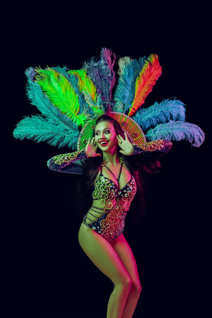 Beautiful young woman in carnival peacock costume. Beauty model woman at party over holiday background with magic glow. Christmas and New Year celebration. Glamour lady with perfect make up and hairstyle Stock Photo - 116259341