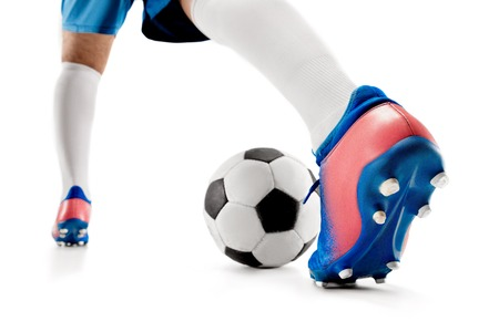 The legs of soccer player close-up isolated on white. Young boy with soccer ball doing flying kick. football soccer player in motion on studio background. Fit boy in action at game.
