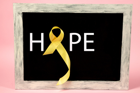 Yellow ribbon symbolic color for Sarcoma Bone cancer awareness and suicide prevention on aged wooden advertising board. The cancer, health, help, care, support, hope, illness, healthcare concept