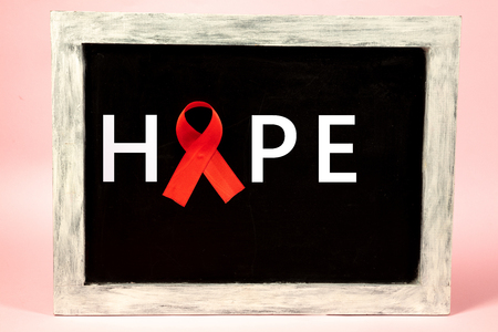 Aids Awareness Sign Red Ribbons on advertising board wooden background. World Aids Day concept. The health, help, care, support, hope, illness, healthcare concept