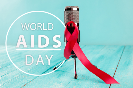 Aids Awareness Sign Red Ribbon with microphone on wooden background . World Aids Day concept. The health, help, care, support, hope, illness, healthcare concept Stock Photo