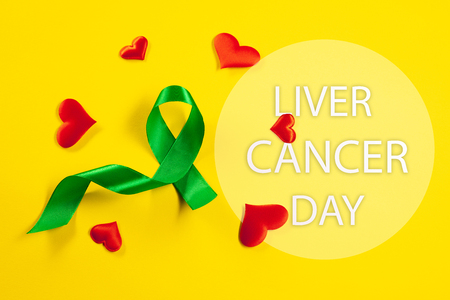 Liver Cancer and Hepatitis B - HVB Awareness month ribbon, Emerald Green or Jade ribbon awareness color on yellow background. The cancer, health, help, care, support, hope, illness, survivor, healthcare concept Stock Photo