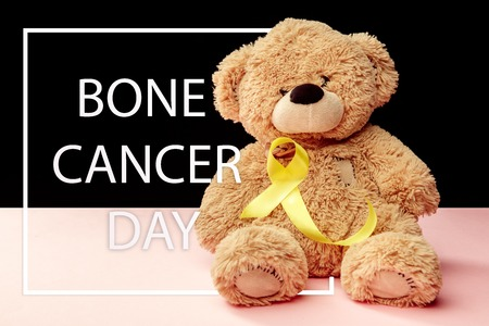 Yellow ribbon symbolic color for Sarcoma Bone cancer awareness and suicide prevention with toy bear. The cancer, health, help, care, support, hope, illness, healthcare concept Stock Photo - 116286010