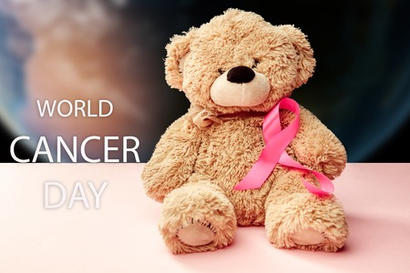 The text world cancer day and a pink ribbon with toy bear on a pink background. The cancer, health, breast, awareness, campaign, disease, help, care, support, hope, illness, survivor and healthcare concept Stock Photo - 116286012