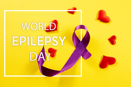 International or world Epilepsy Day concept. The text and a purple ribbon on a yellow background. The health, breast, awareness, campaign, disease, help, care, support, hope, illness, survivor and healthcare concept