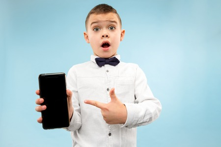 Indoor portrait of attractive young boy isolated on blue background, holding blank smartphone, smiling at camera, showing screen, feeling happy and surprised. Human emotions, facial expression concept. Stock Photo