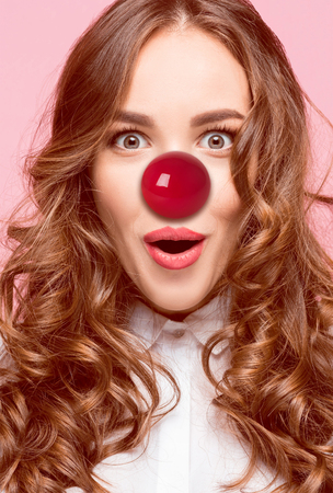 The happy surprised and smiling woman on red nose day. The clown, fun, party, celebration, funny, joy, holiday, comic, emotion, fool and humor concept Stock Photo