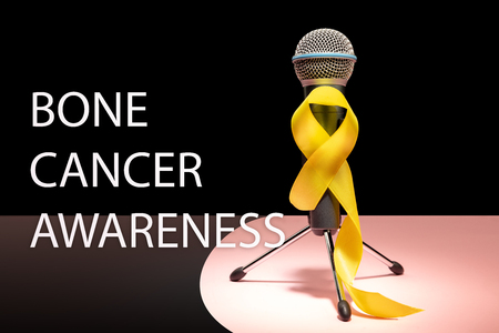 Yellow ribbon symbolic color for Sarcoma Bone cancer awareness and suicide prevention with microphone. The cancer, health, help, care, support, hope, illness, healthcare concept