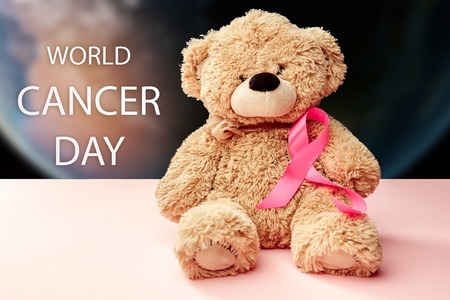 The text world cancer day and a pink ribbon with toy bear on a pink background. The cancer, health, breast, awareness, campaign, disease, help, care, support, hope, illness, survivor and healthcare concept Stock Photo