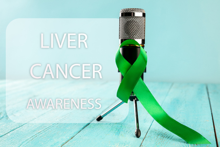Liver Cancer and Hepatitis B - HVB Awareness month ribbon, Emerald Green or Jade ribbon awareness color on wooden background. The cancer, health, help, care, support, hope, illness, survivor, healthcare concept