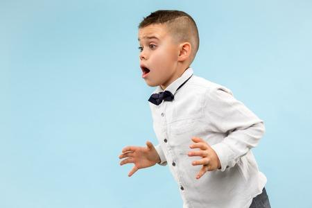 Guau. Retrato frontal de medio cuerpo masculino atractivo sobre fondo de color azul de estudio. Muchacho adolescente sorprendido emocional joven que se coloca con la boca abierta. Las emociones humanas, el concepto de expresión facial. Colores de moda Foto de archivo