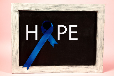 Colon cancer awareness poster. Blue ribbon made of dots on black board background. The cancer, health, breast, awareness, campaign, disease, help, care, support, hope illness and healthcare concept 스톡 콘텐츠
