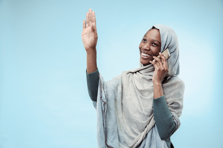 The beautiful young black african muslim girl wearing gray hijab at blue studio. She standing with mobile phone with a happy smile on her face. The human emotions, facial expression concept. Trendy colors Stock Photo