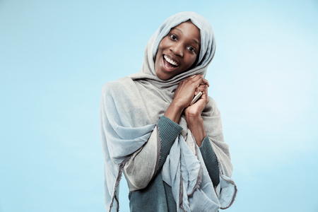 The beautiful young black african muslim girl wearing gray hijab at blue studio. She standing with mobile phone with a happy smile on her face. The human emotions, facial expression concept. Trendy colors Фото со стока