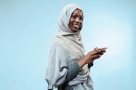 Das schöne junge schwarzafrikanische muslimische Mädchen mit grauem Hijab im blauen Studio. Sie steht mit Handy mit einem glücklichen Lächeln im Gesicht. Die menschlichen Emotionen, Gesichtsausdruckkonzept. Trendige Farben Standard-Bild