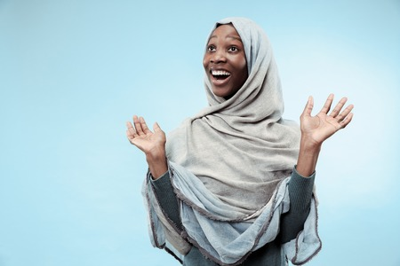 Piękna młoda czarna afrykańska muzułmańska dziewczyna ubrana w szary hidżab w niebieskim studio. Stoi ze szczęśliwym uśmiechem na twarzy. Ludzkie emocje, koncepcja wyraz twarzy. Modne kolory Zdjęcie Seryjne