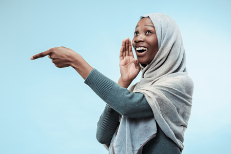Secret, gossip concept. Young african woman whispering a secret behind her hand. The woman isolated on trendy blue studio background. Young emotional woman. Human emotions, facial expression concept. Stock Photo