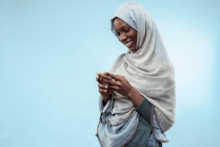 Das schöne junge schwarzafrikanische muslimische Mädchen mit grauem Hijab im blauen Studio. Sie steht mit Handy mit einem glücklichen Lächeln im Gesicht. Die menschlichen Emotionen, Gesichtsausdruckkonzept. Trendige Farben