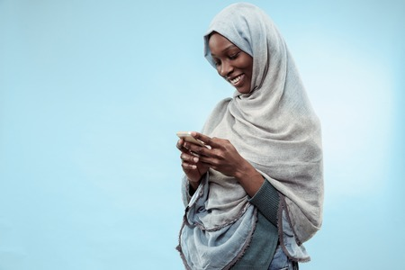 The beautiful young black african muslim girl wearing gray hijab at blue studio. She standing with mobile phone with a happy smile on her face. The human emotions, facial expression concept. Trendy colors Archivio Fotografico