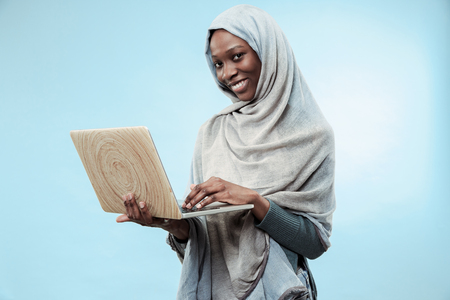 Portrait Of Female University Student Working on laptop. The beautiful young black african muslim girl wearing gray hijab at blue studio. She standing with happy smile on her face. Stock Photo
