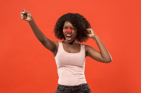 The happy surprised and smiling african woman on red nose day. The clown, fun, party, celebration, funny, joy, holiday, humor concept Imagens