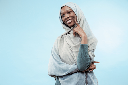 The beautiful young black african muslim girl wearing gray hijab at blue studio. She standing with a happy smile on her face. The human emotions, facial expression concept. Trendy colors