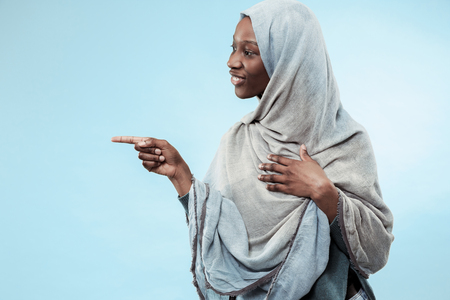 The beautiful young black african muslim girl wearing gray hijab at blue studio. She pointing to left and standing with a happy smile on her face. The human emotions, facial expression concept. Trendy colors Stock Photo