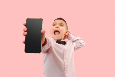Indoor portrait of attractive young boy isolated on pink background, holding blank smartphone, smiling at camera, showing screen, feeling happy and surprised. Human emotions, facial expression concept.