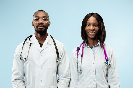 The female and male smiling happy afro american doctors on blue background at studio.The clinic, medical, nurse, health, healthcare, hospital, care, job, professional concept
