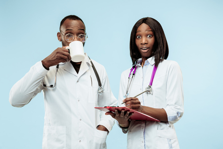 The female and male surprised afro american doctors on blue background at studio.The clinic, medical, nurse, health, healthcare, hospital, care, job, professional concept Stock Photo