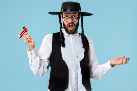Portrait of a young orthodox Hasdim Jewish man with wooden Grager Ratchet at Jewish festival of Purim at studio. The purim, jewish, festival, holiday, celebration, judaism, pastry, tradition, cookie, religion concept. Stock Photo