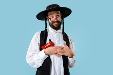 Portrait of a young orthodox Hasdim Jewish man with wooden Grager Ratchet at Jewish festival of Purim at studio. The purim, jewish, festival, holiday, celebration, judaism, pastry, tradition, cookie, religion concept.