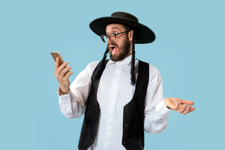 Portrait of a young orthodox Hasdim Jewish man with mobile phone at Jewish festival of Purim at studio. The purim, jewish, festival, holiday, celebration, judaism, pastry, tradition, cookie, religion concept. Stock Photo