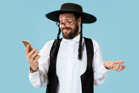 Portrait of a young orthodox Hasdim Jewish man with mobile phone at Jewish festival of Purim at studio. The purim, jewish, festival, holiday, celebration, judaism, pastry, tradition, cookie, religion concept. Zdjęcie Seryjne