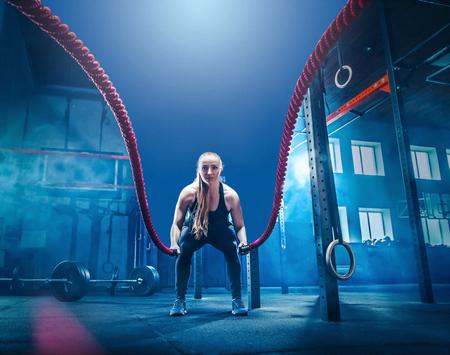 La donna con la battaglia della corda della battaglia si esercita nella palestra di forma fisica. concetto di CrossFit. palestra, sport, corda, allenamento, atleta, allenamento, esercizi concept Archivio Fotografico