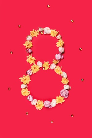 The conceptual composition from flowers about Eights march womans day, holiday on a red background. The number 8 in decor. Top view Reklamní fotografie