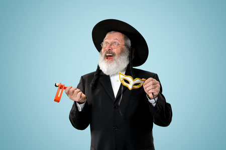 Portrait of a senior orthodox Hasdim Jewish man with wooden Grager Ratchet at Jewish festival of Purim at studio. The purim, jewish, festival, holiday, celebration, judaism, pastry, tradition, cookie, religion concept.