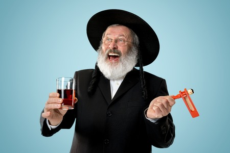 Portrait of old senior orthodox Hasdim Jewish man with wooden Grager Ratchet at Jewish festival of Purim at studio. The purim, jewish, festival, holiday, celebration, judaism, pastry, tradition, cookie, religion concept.