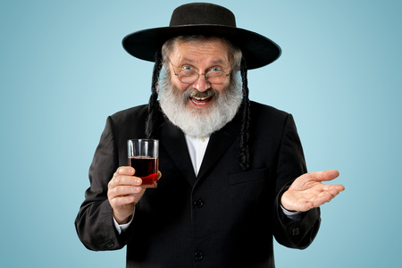 Portrait of old senior orthodox Hasdim Jewish man with kosher wine at Jewish festival of Purim at studio. The purim, jewish, festival, holiday, celebration, judaism, pastry, tradition, cookie, religion concept.