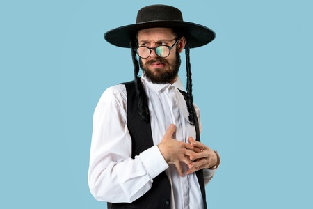 Portrait of a young orthodox Hasdim Jewish man at Jewish festival of Purim at studio. The purim, jewish, festival, holiday, celebration, judaism, tradition, religion concept.