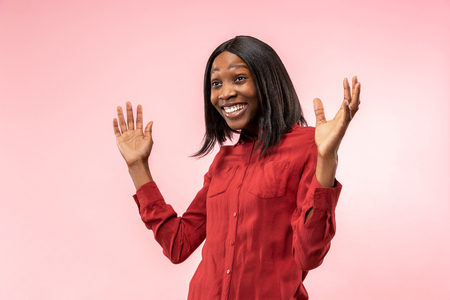 Happy business woman standing and smiling isolated on red studio background. Beautiful female half-length portrait. Young emotional afro woman. The human emotions, facial expression concept. Front view. Banco de Imagens