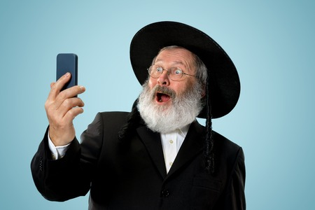 Portrait of old senior orthodox Hasdim Jewish man with mobile phone at Jewish festival of Purim at studio. The purim, jewish, festival, holiday, celebration, judaism, tradition, business, communication, religion concept. Stock Photo