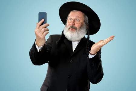 Portrait of old senior orthodox Hasdim Jewish man with mobile phone at Jewish festival of Purim at studio. The purim, jewish, festival, holiday, celebration, judaism, tradition, business, communication, religion concept. 免版税图像